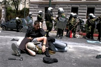 ATHENS, GREECE - MAY 11: Protesters lay on the street after clashes with riot police during a 24-hour strike in Athens, Wednesday, May 11, 2011. Riot police made heavy use of tear gas and stun grenades to disperse youths throwing stones and petrol bombs during a march attended by 20,000 people to protest the Greek government's harsh austerity measures.(Photo by Milos Bicanski/Getty Images)