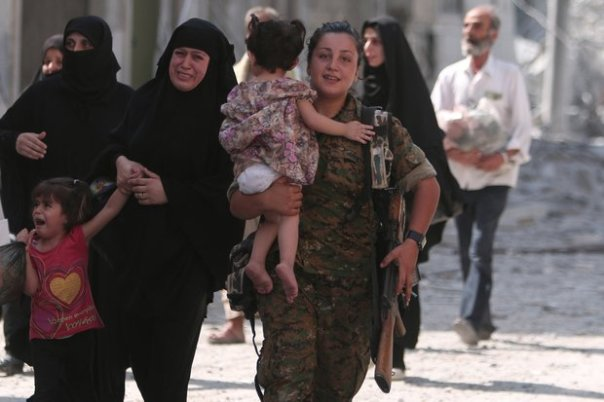 SDF-soldier-helps-civilians-to-safet-in-Manbij-Reuters