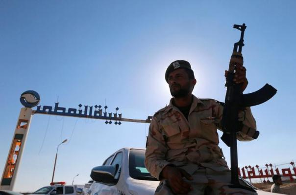 Member of Libyan forces loyal to eastern commander Khalifa Haftar holds a weapon as he sits on a car in front of the gate at Zueitina oil terminal in Zueitina, west of Benghazi