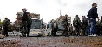 Syrian security forces and locals gather at the scene of a bombing following twin attacks targeting Shiite pilgrims in Damascus' Old City on March 11, 2017, in one of the bloodiest attacks in the Syrian capital. A roadside bomb detonated as a bus passed and a suicide bomber blew himself up in the Bab al-Saghir area, which houses several Shiite mausoleums that draw pilgrims from around the world, the Syrian Observatory for Human Rights said. / AFP PHOTO / Louai Beshara (Photo credit should read LOUAI BESHARA/AFP/Getty Images)