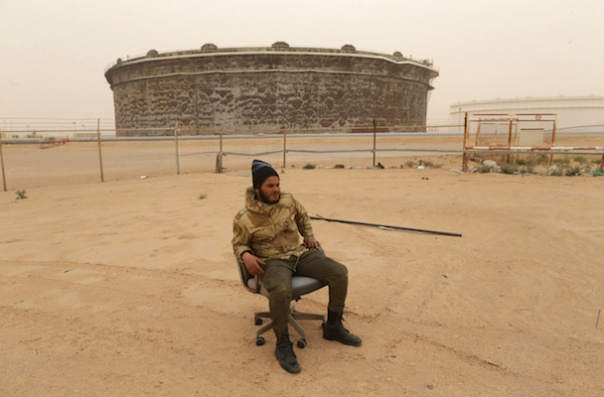 Member of Libyan National Army (LNA) sits on a chair as he guards oil tanks after they were recaptured from fighters of Benghazi Defence Brigades (BDB) south of Ras Lanuf