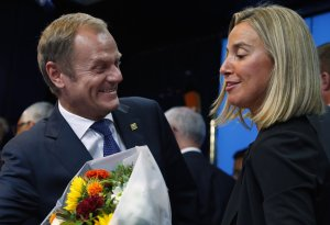 Newly elected European Council President Donald Tusk and newly elected European High Representative for Foreign Affairs Minister Federica Mogherini talk together during a EU summit in Brussels