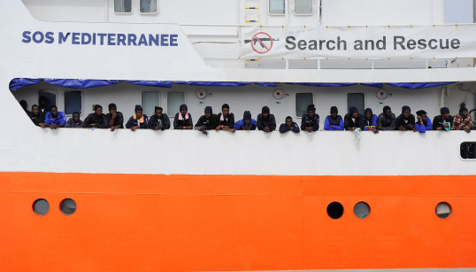 Migrants wait to disembark from Aquarius in the Sicilian harbour of Catania
